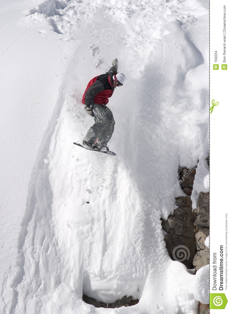 Snowboard jump from a cliff in the powder