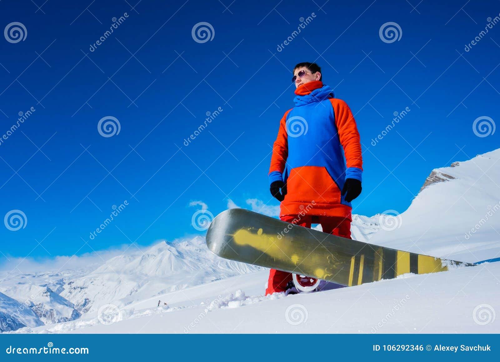Snowboarder à moda do atleta na perspectiva das montanhas da neve