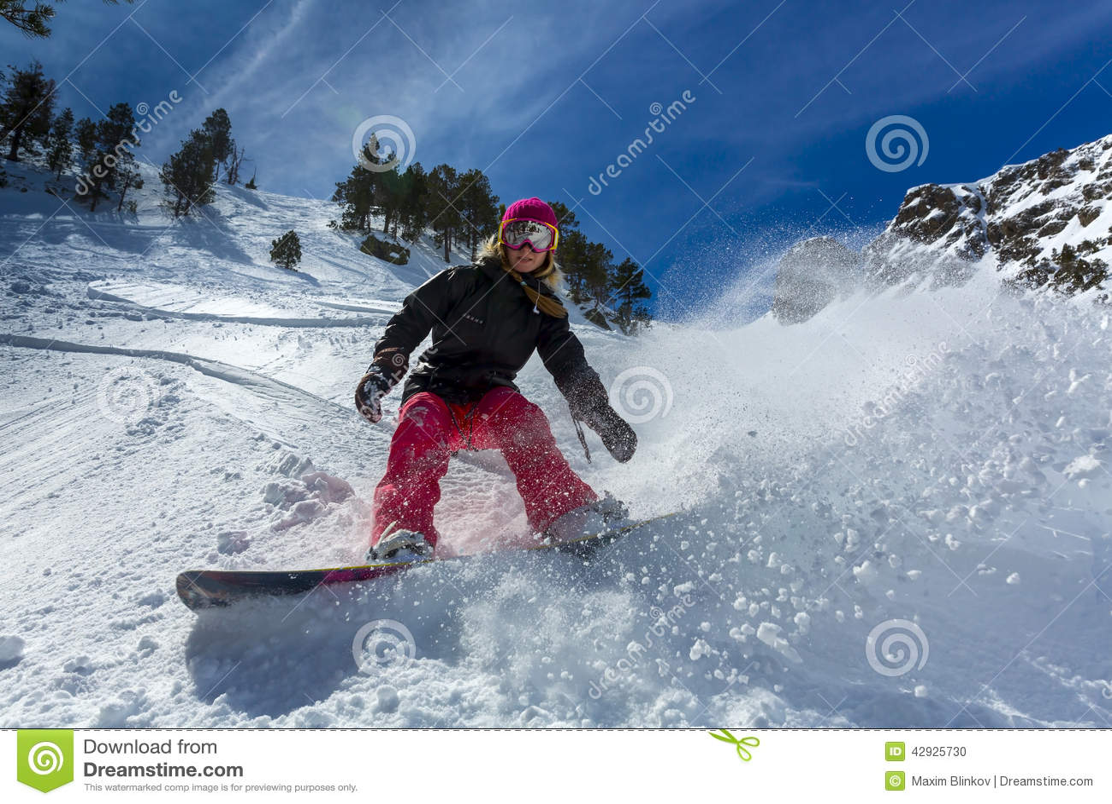 Snowboarder de la mujer en el movimiento en montañas