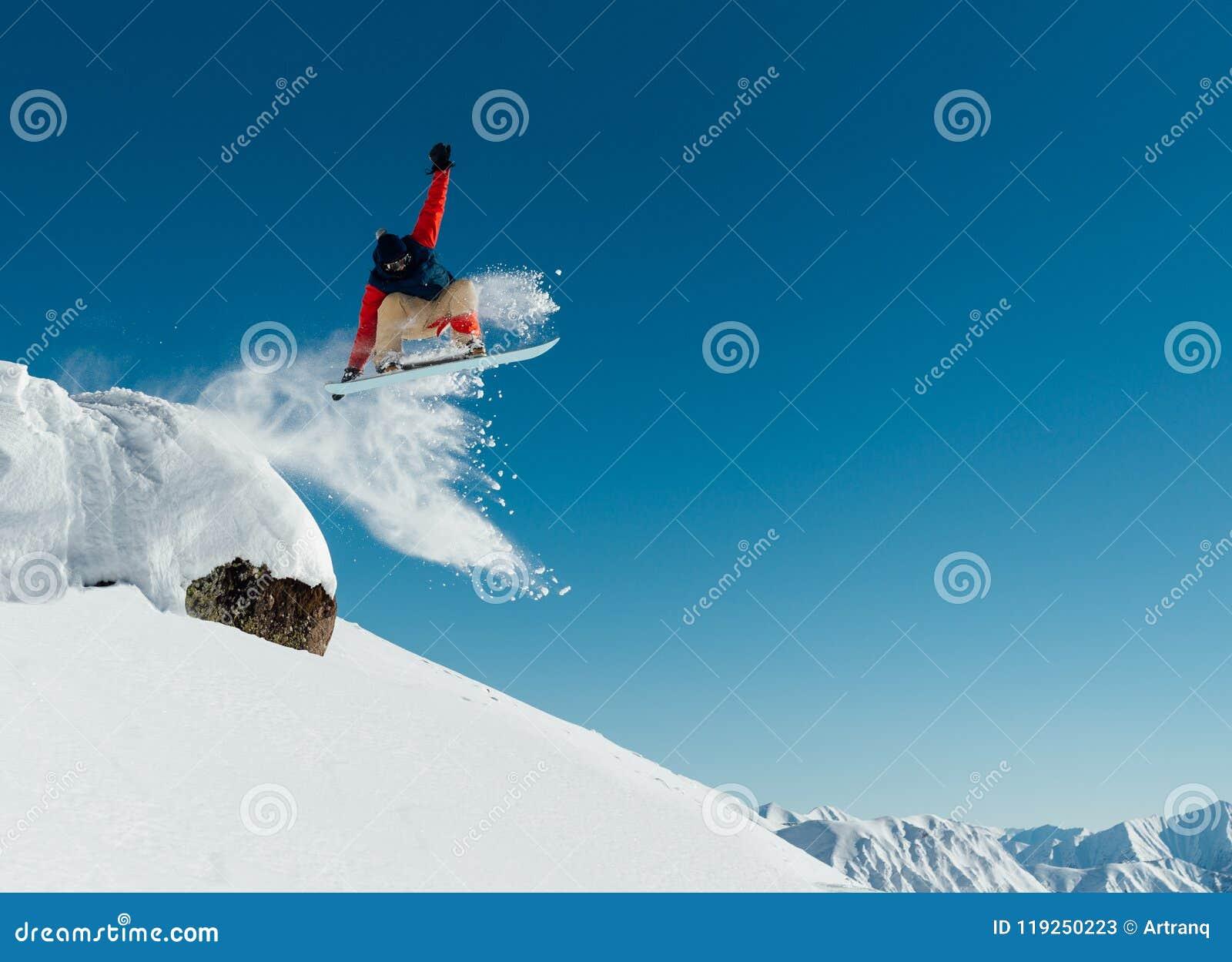 Snowboarder in de uitrustingsdalingen van de richel van de steen ont
