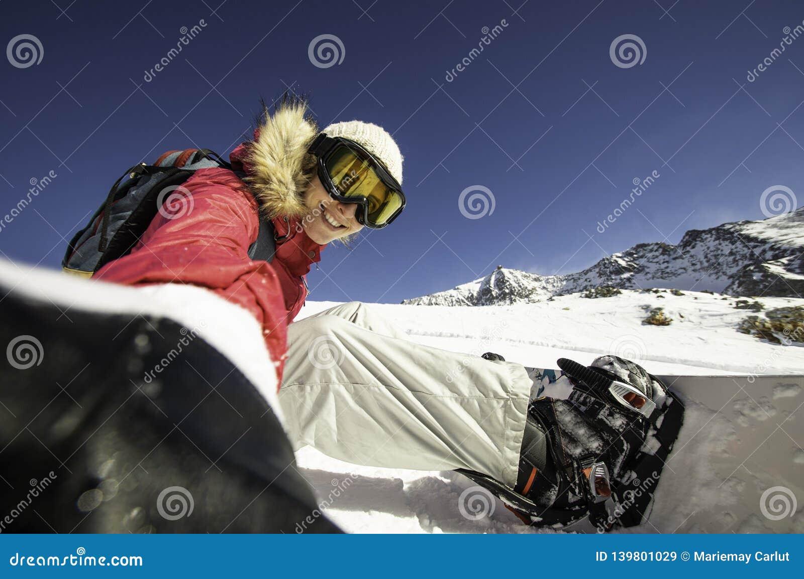 Snowboarder di Selfie Giovane donna felice che prende selfie su un pendio in alpi del nord, Francia