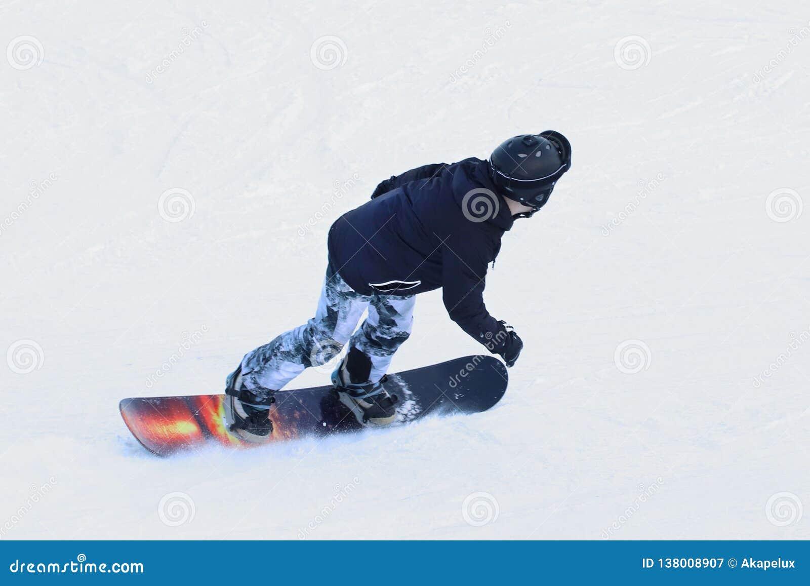 Snowboarder die op een snowboard onderaan de snow-covered helling bij een skitoevlucht berijden De sport van de winter Vrij slag