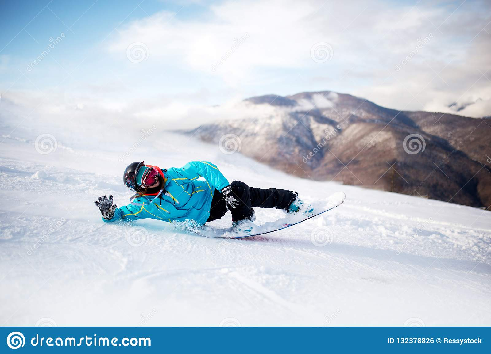 Snowboarder in high mountains during sunny day lay on snow.