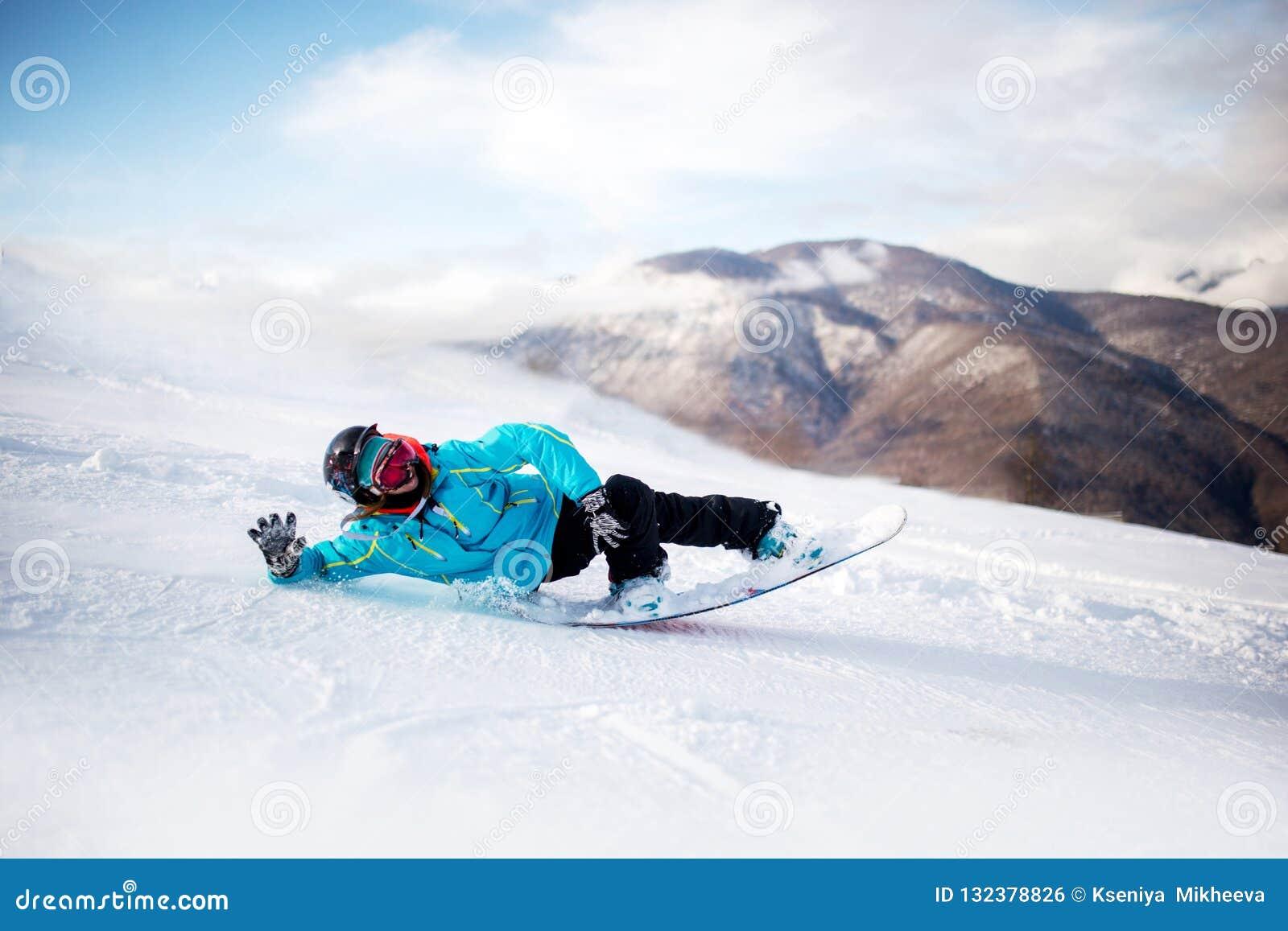 Snowboarder in hooggebergte tijdens zonnige dag legt op sneeuw