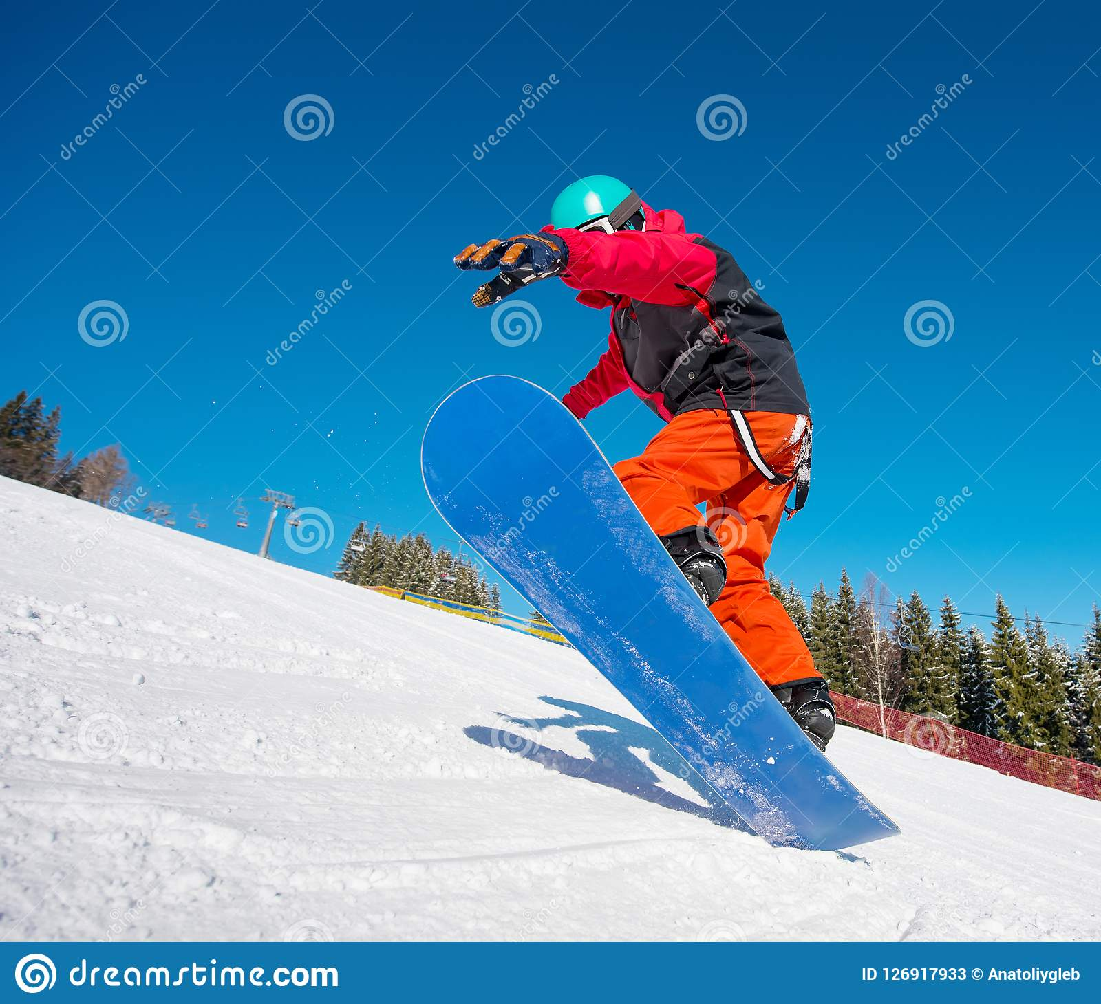 Snowboarder Jumping In The Air While Riding On The Slope At