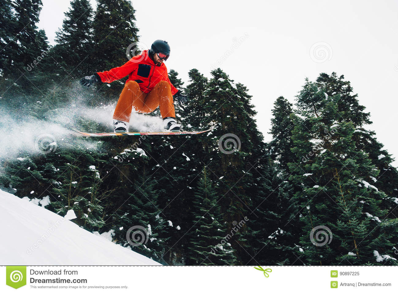snowboarder is jumping very high and freeriding from hill in the