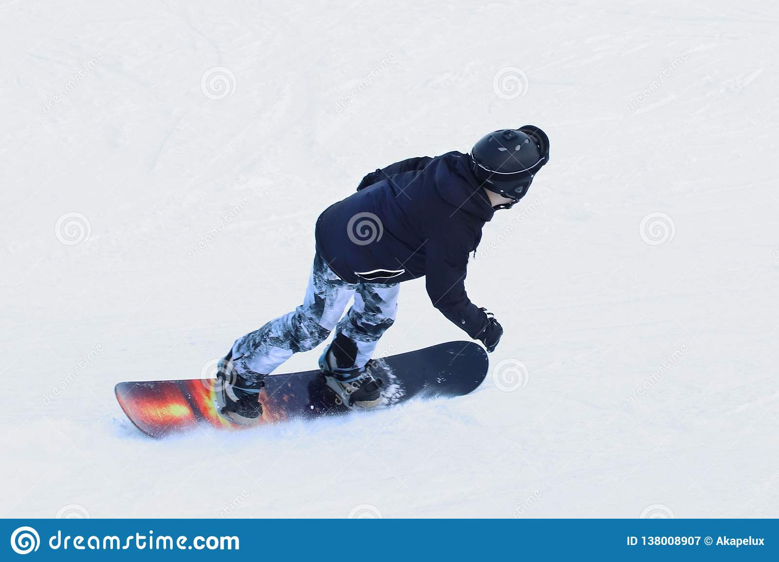 Snowboarder Riding On A Snowboard Down The Snow Covered