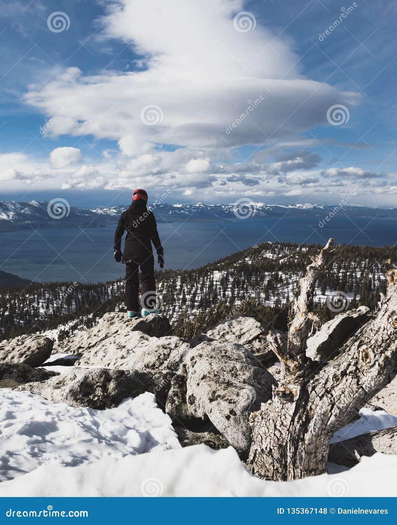 Snowboarder stoi samotnie przy szczytem ono wpatruje się w dół na Jeziornego Tahoe i śnieg Nakrywał góry