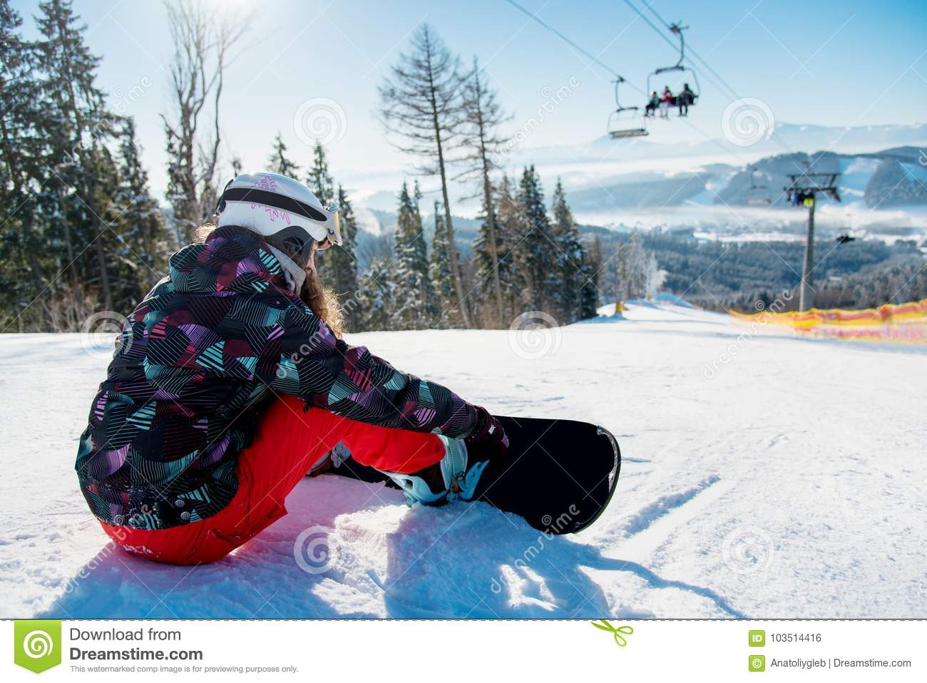Snowboarder woman resting on ski slope under the lift