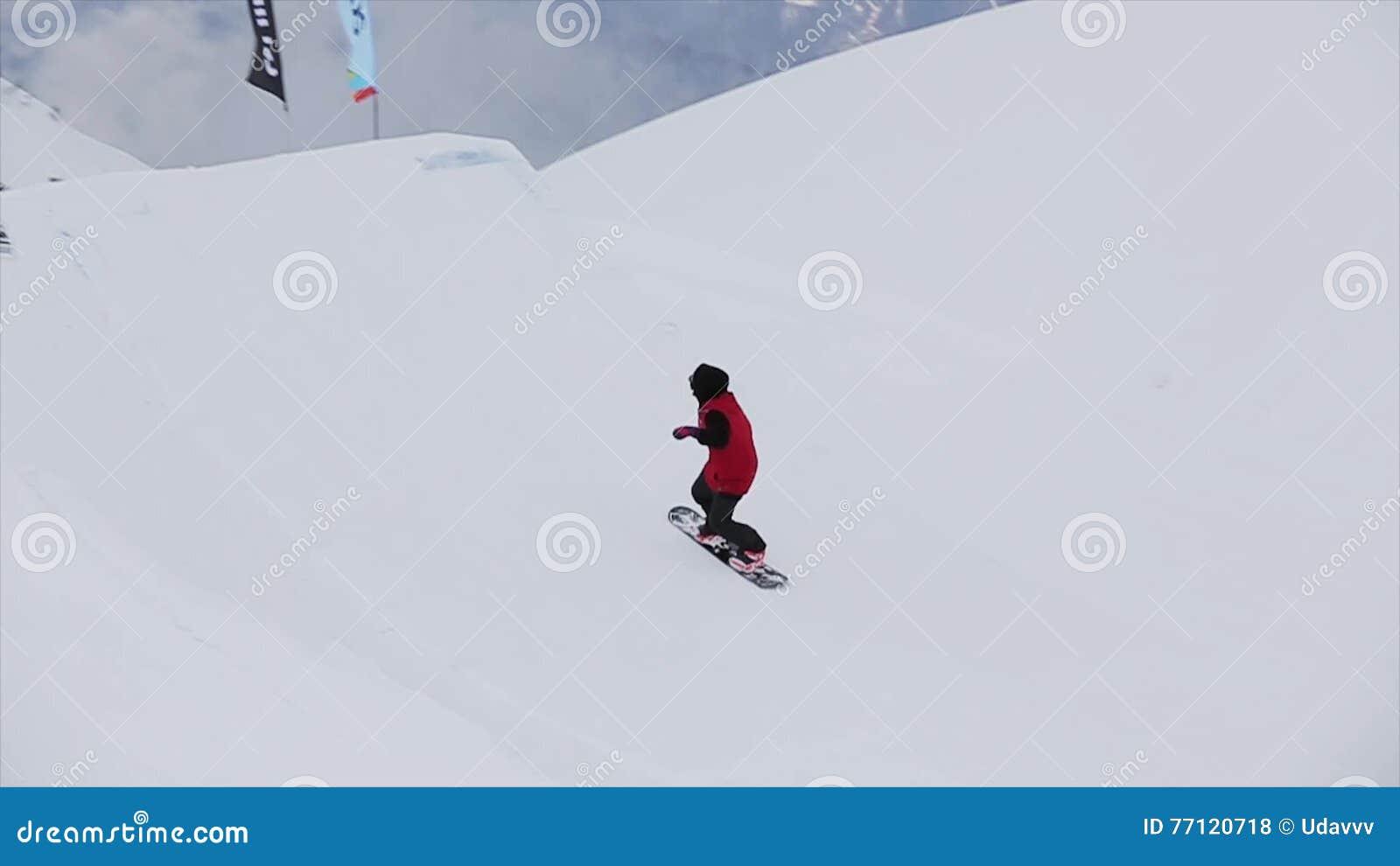 Snowboarderen gör extrem höjdhopp i luften från språngbrädan i snöberg jippo challenge arkivfilmer