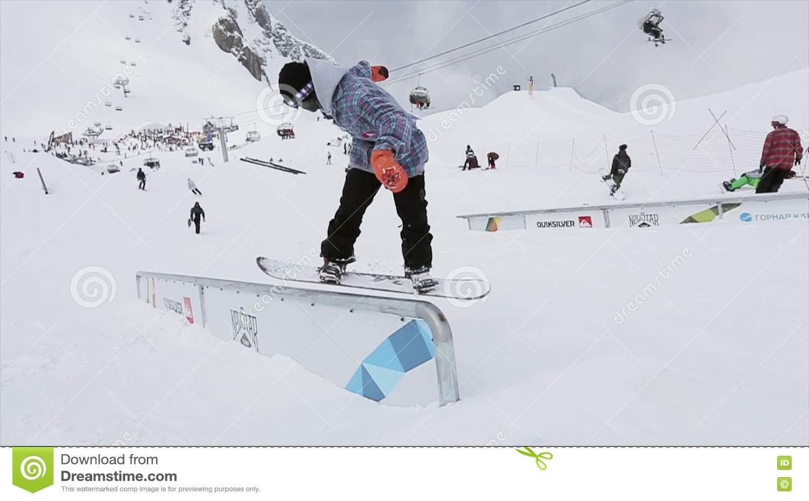 Snowboarderen gör tillbaka glidbanan på järnslinga på lutning folk snöig berg konkurrens challenge arkivfilmer
