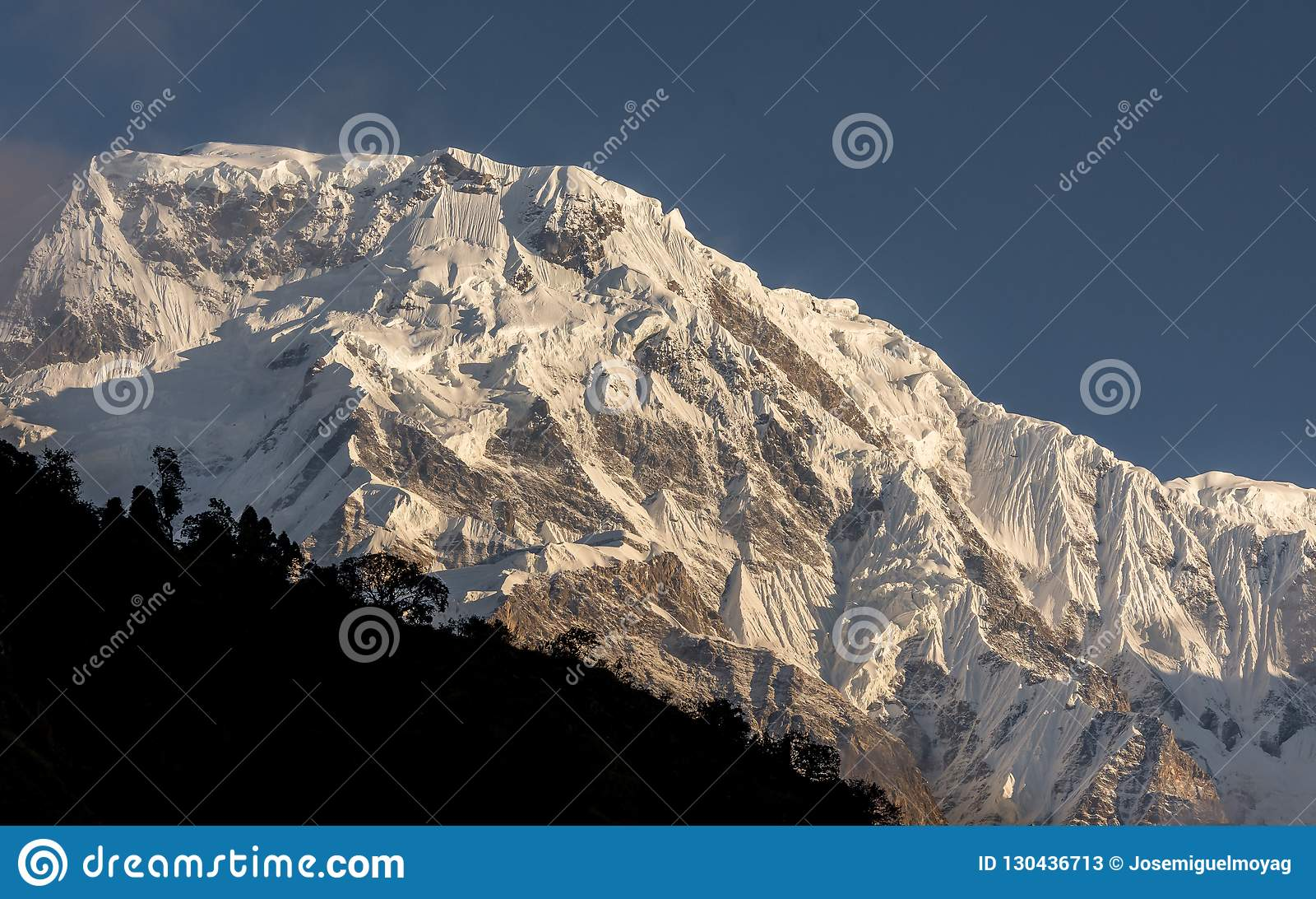 Snowcapped de bergtop van het Annapurnazuiden tegen blauwe hemel in Annapurna-de Trekking van het Basiskamp