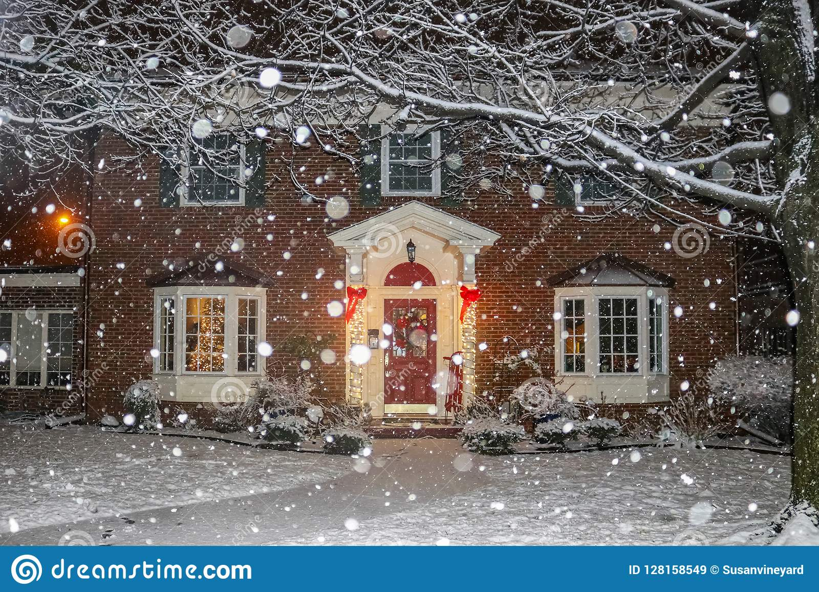 Snowfall On Beautiful Brick House With Columns And Bay Windows With ...