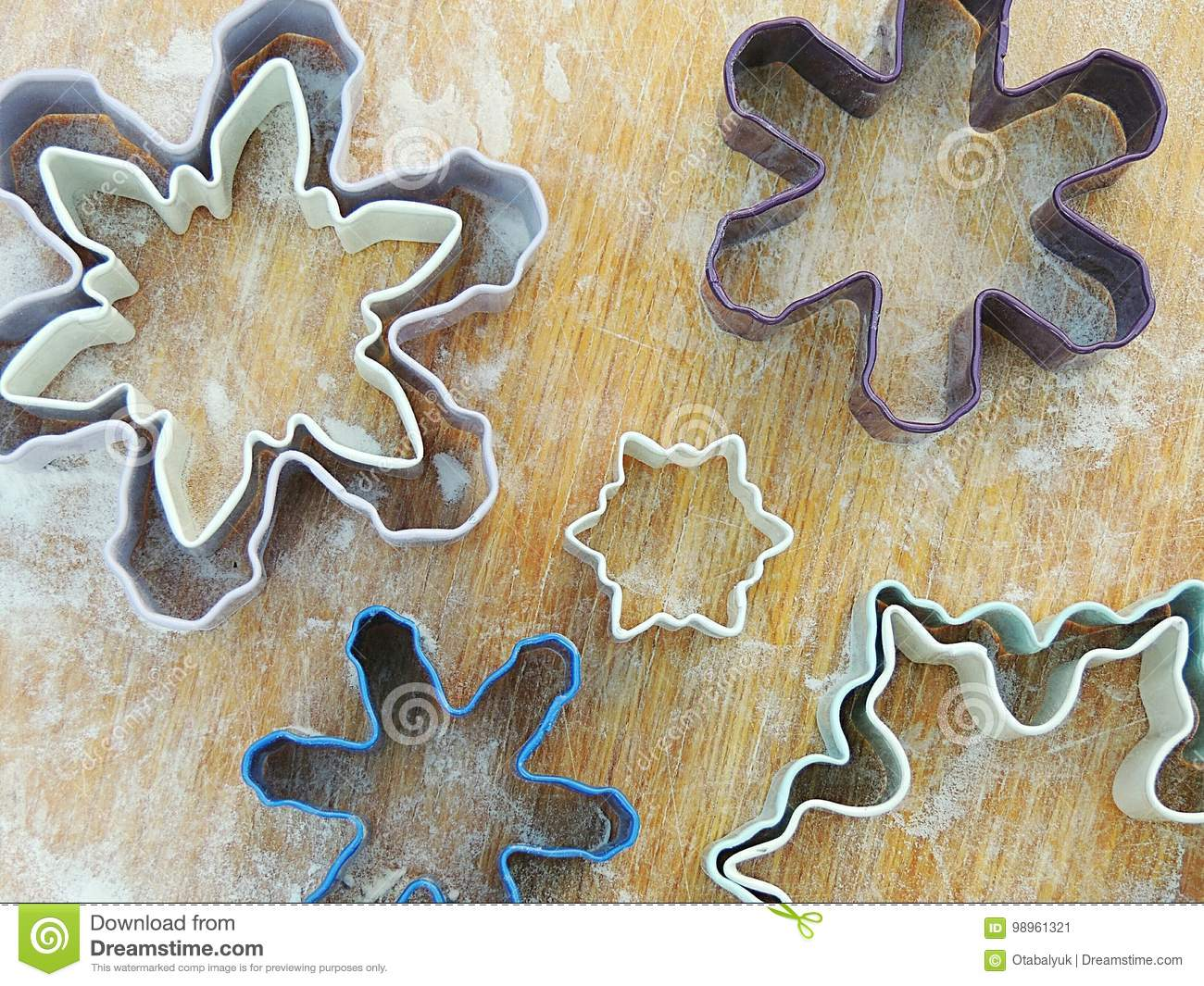 Snowflake Shape Cookies Cutters On Vintage Wooden Board For