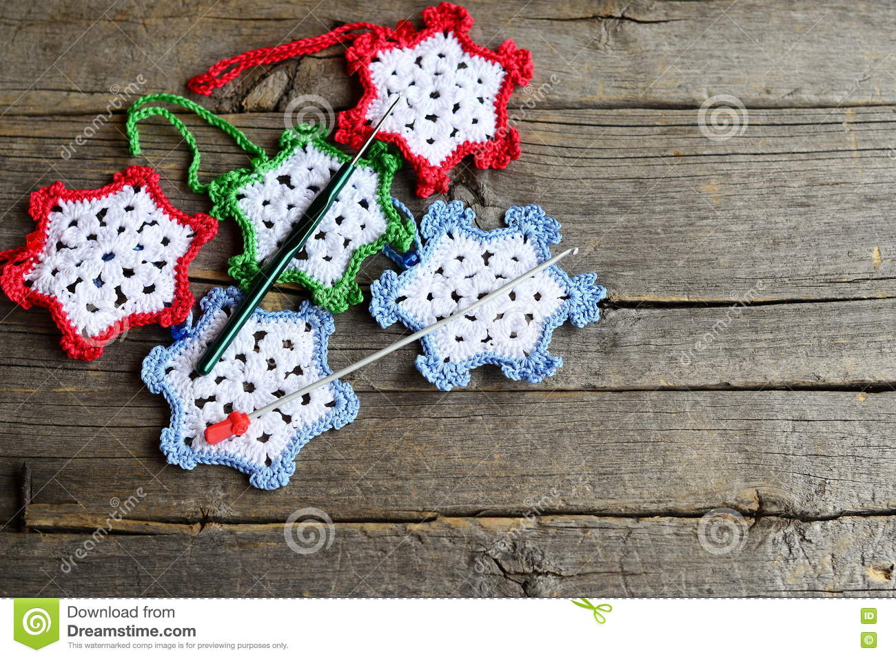 Snowflakes crocheted from cotton yarn, two hooks on an old wooden background with copy space for text. Easy winter crafts
