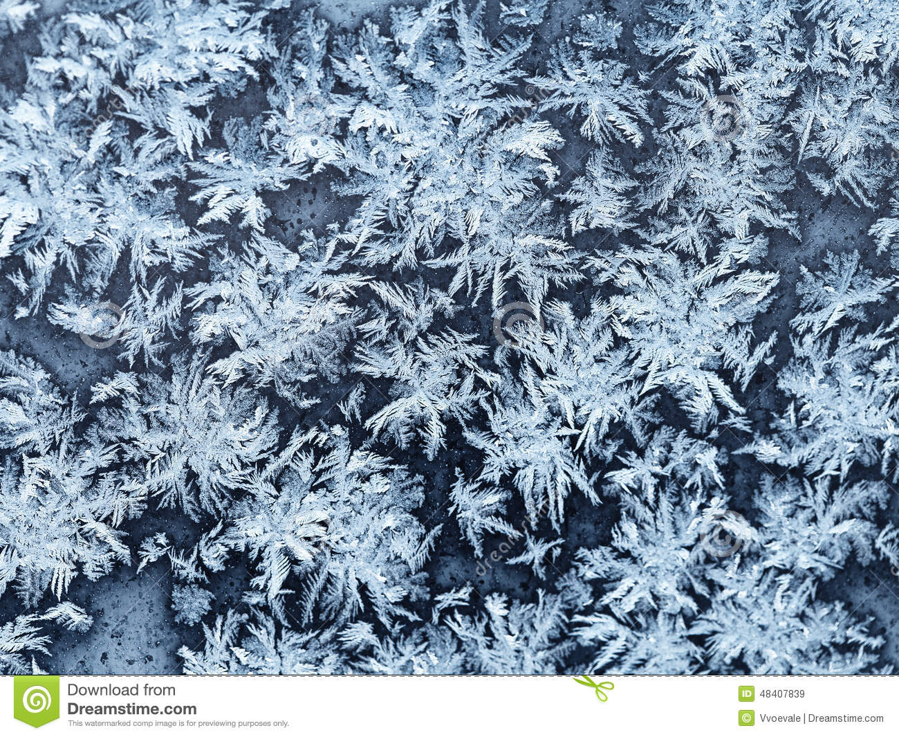 snowflakes and frost on window pane close up stock photo
