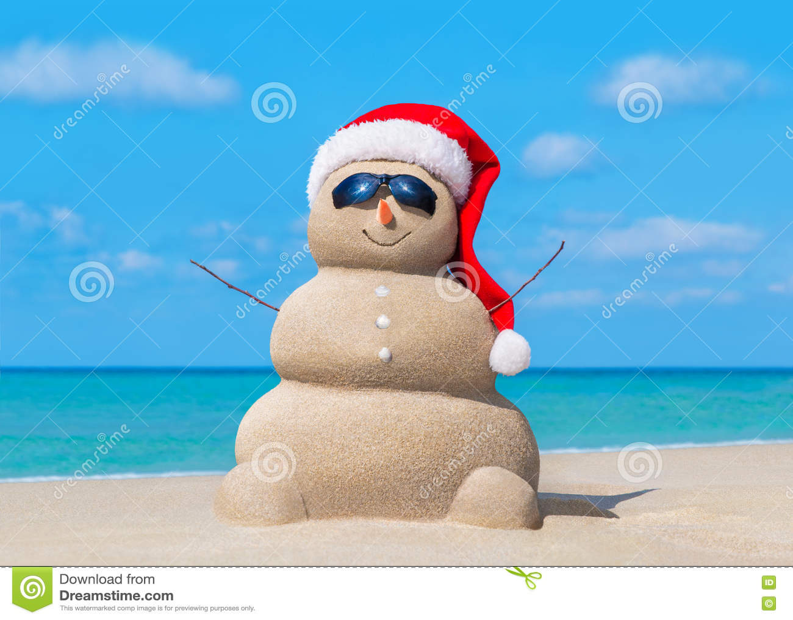 Snowman in Christmas Santa hat and sunglasses at ocean beach