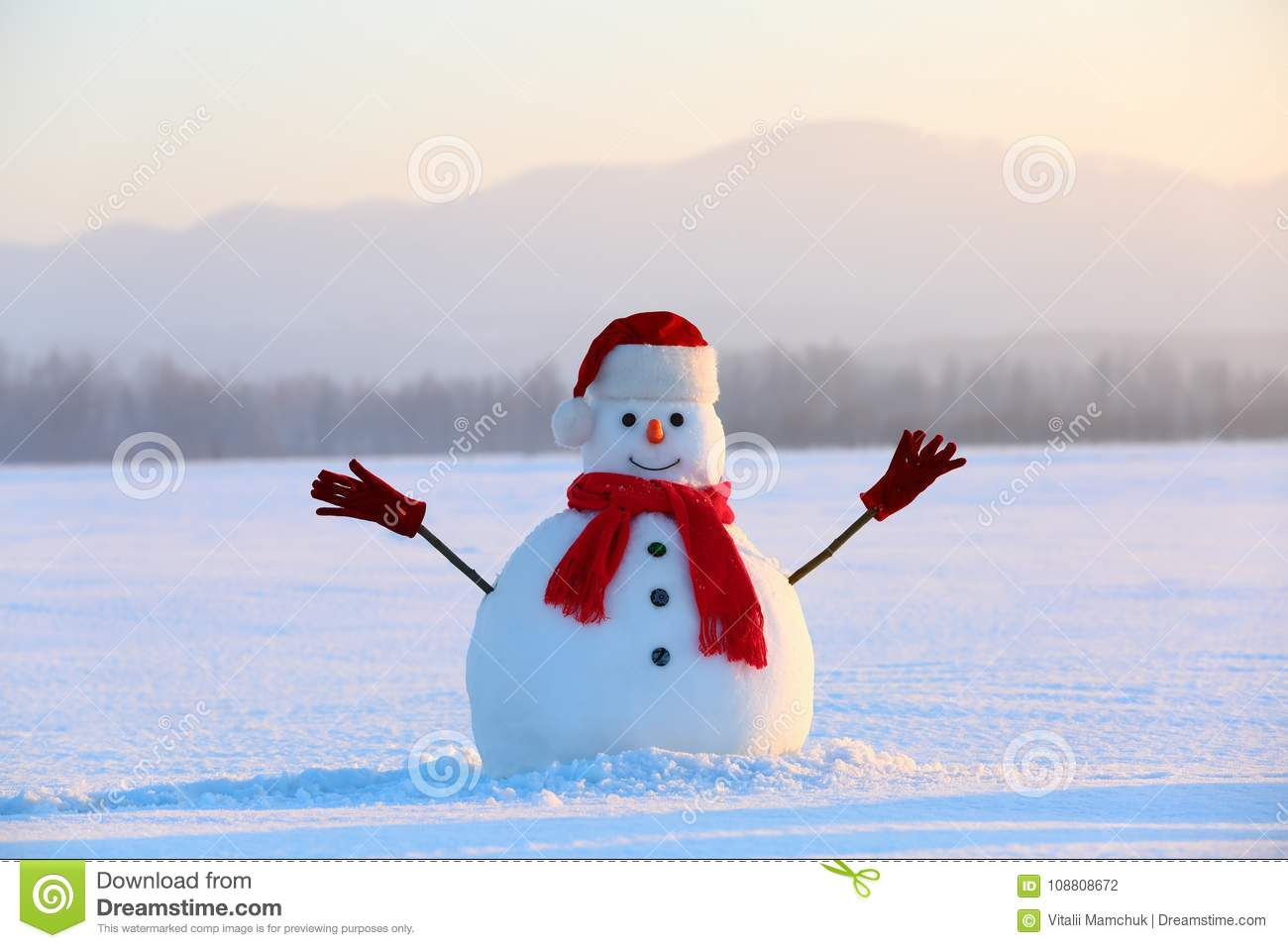 Snowman in red hat and scarf. Christmas scenery. High mountains at the background. Ground covered by snow.