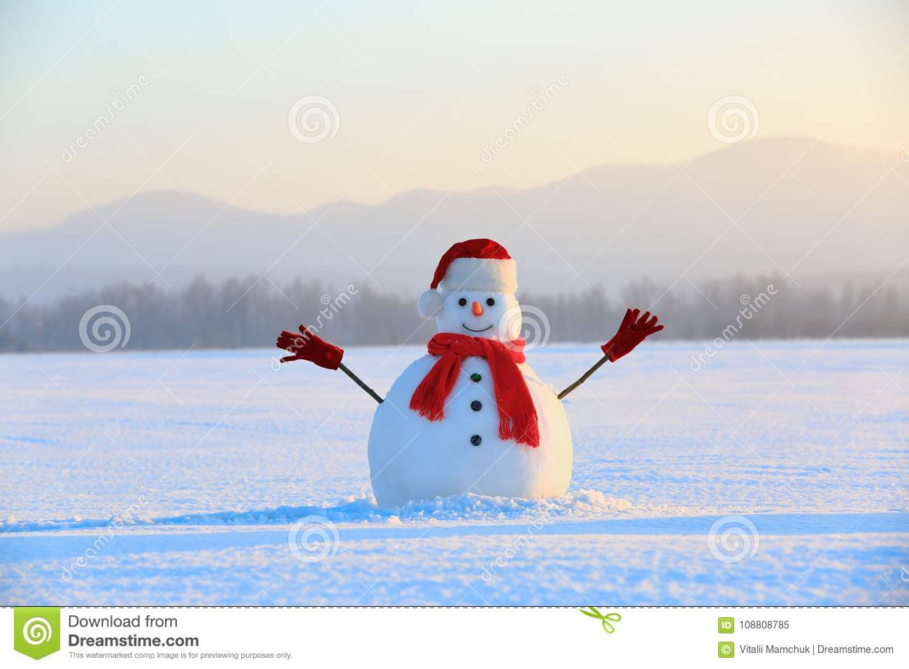Snowman in red hat and scarf. Christmas scenery. High mountains at the background.