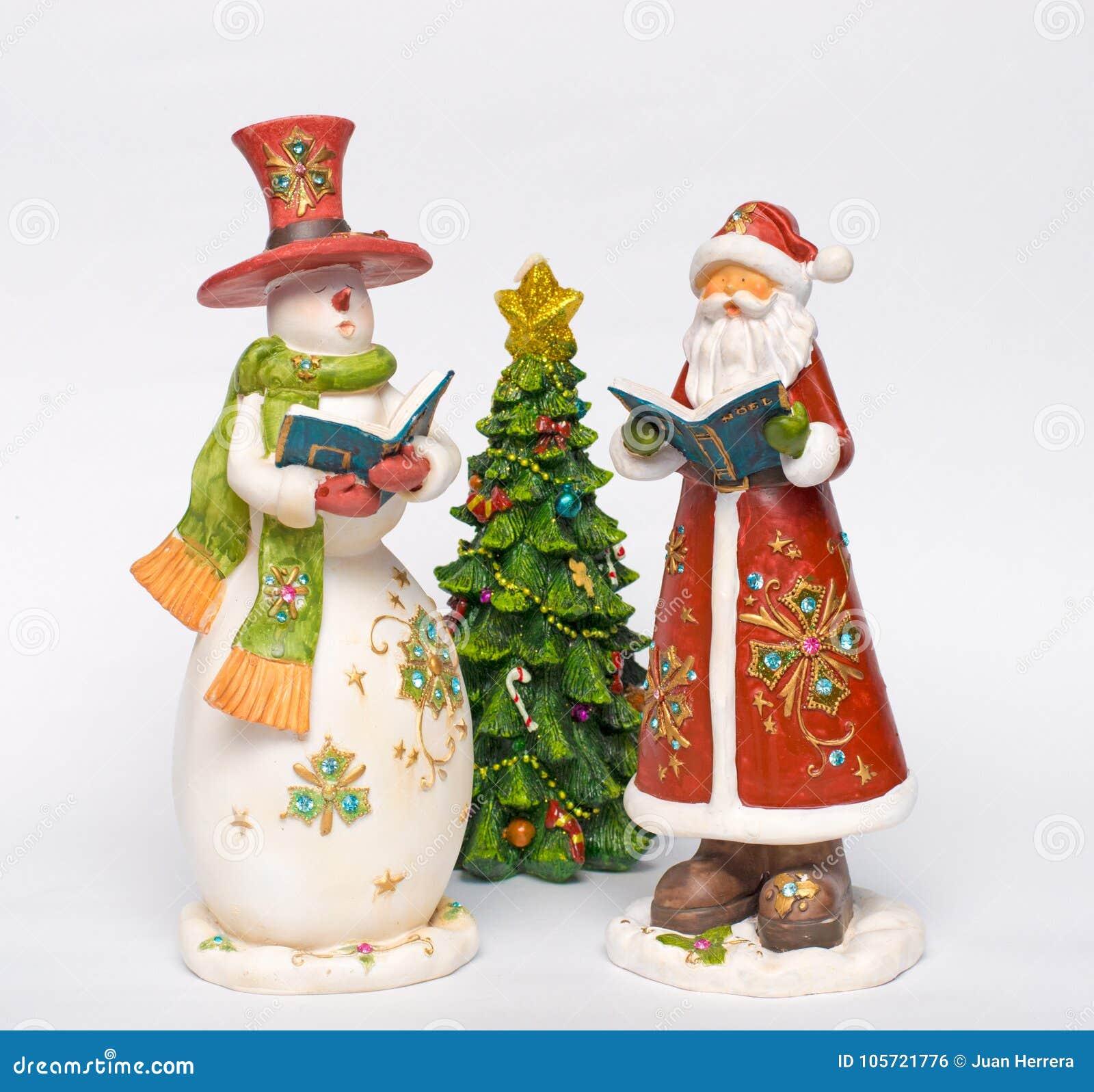 Christmas Carol Singers Figurines.Snowman And Santa Singing Christmas Carols Stock Photo