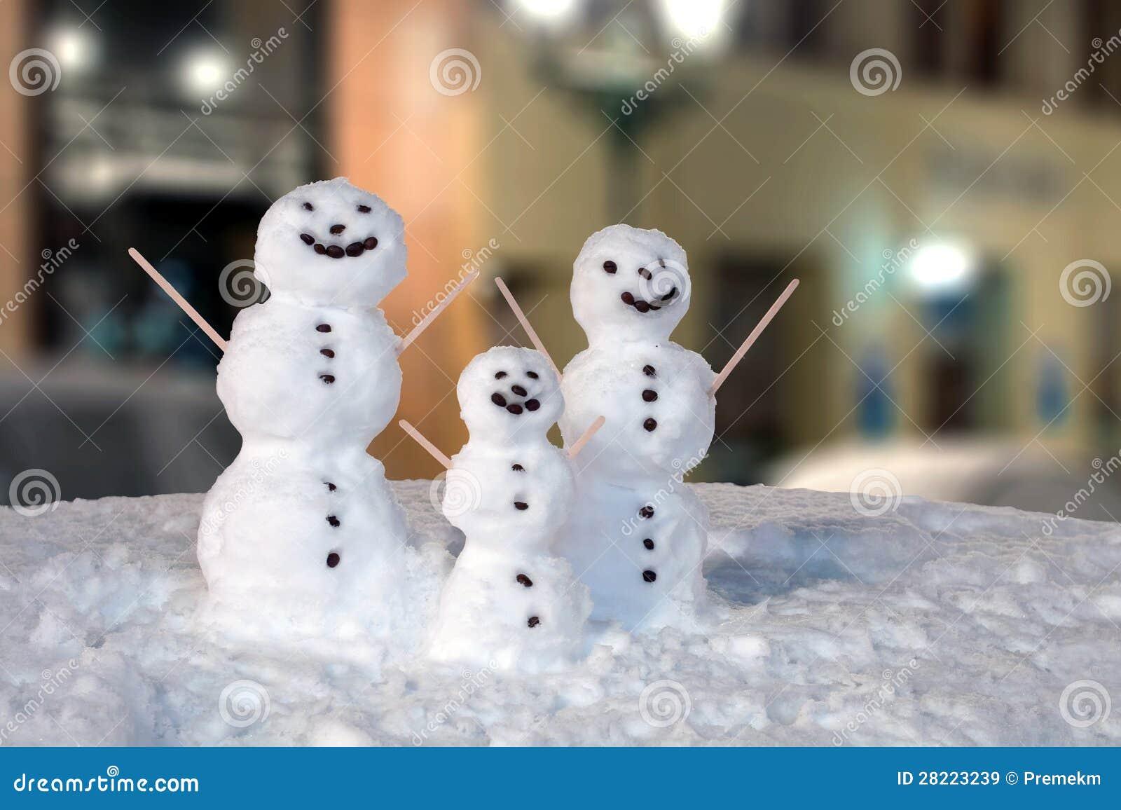 Snowmanfamilj som dekoreras med kaffekorn och träpinnar