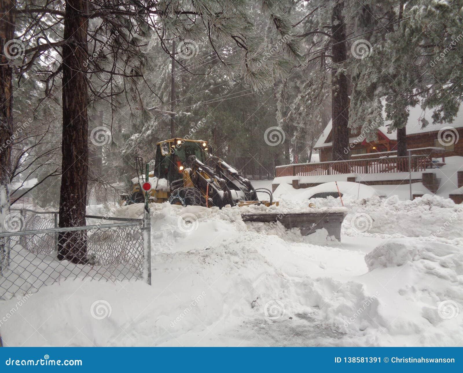 Snowplow Rozjaśnia Mieszkaniową ulicę w Działających wiosnach, San Bernardino góry CA