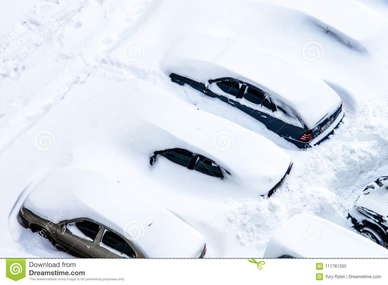 After a snowstorm, cars in the parking lot are covered with a th