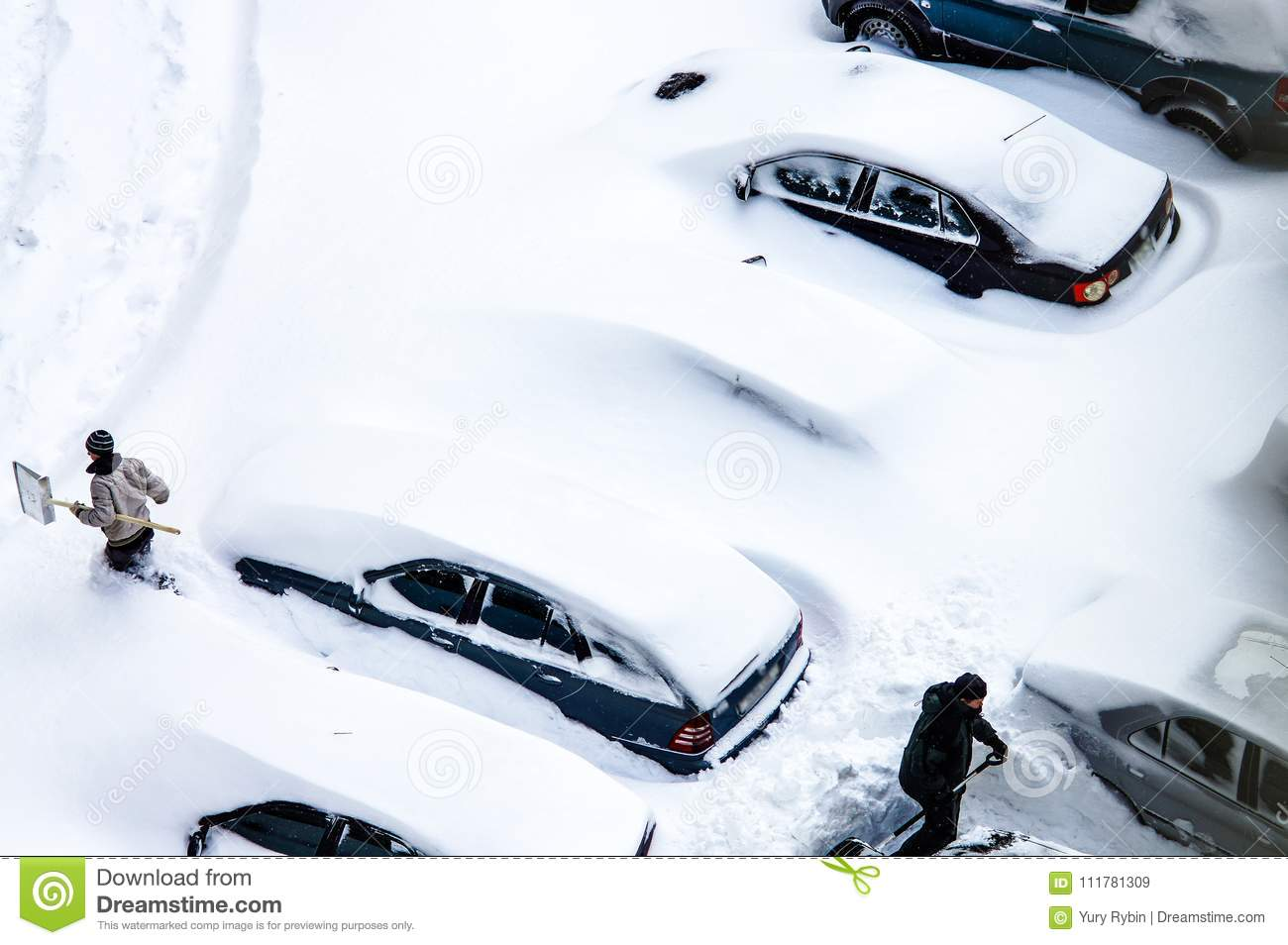 After a snowstorm, people dig out cars from under snow