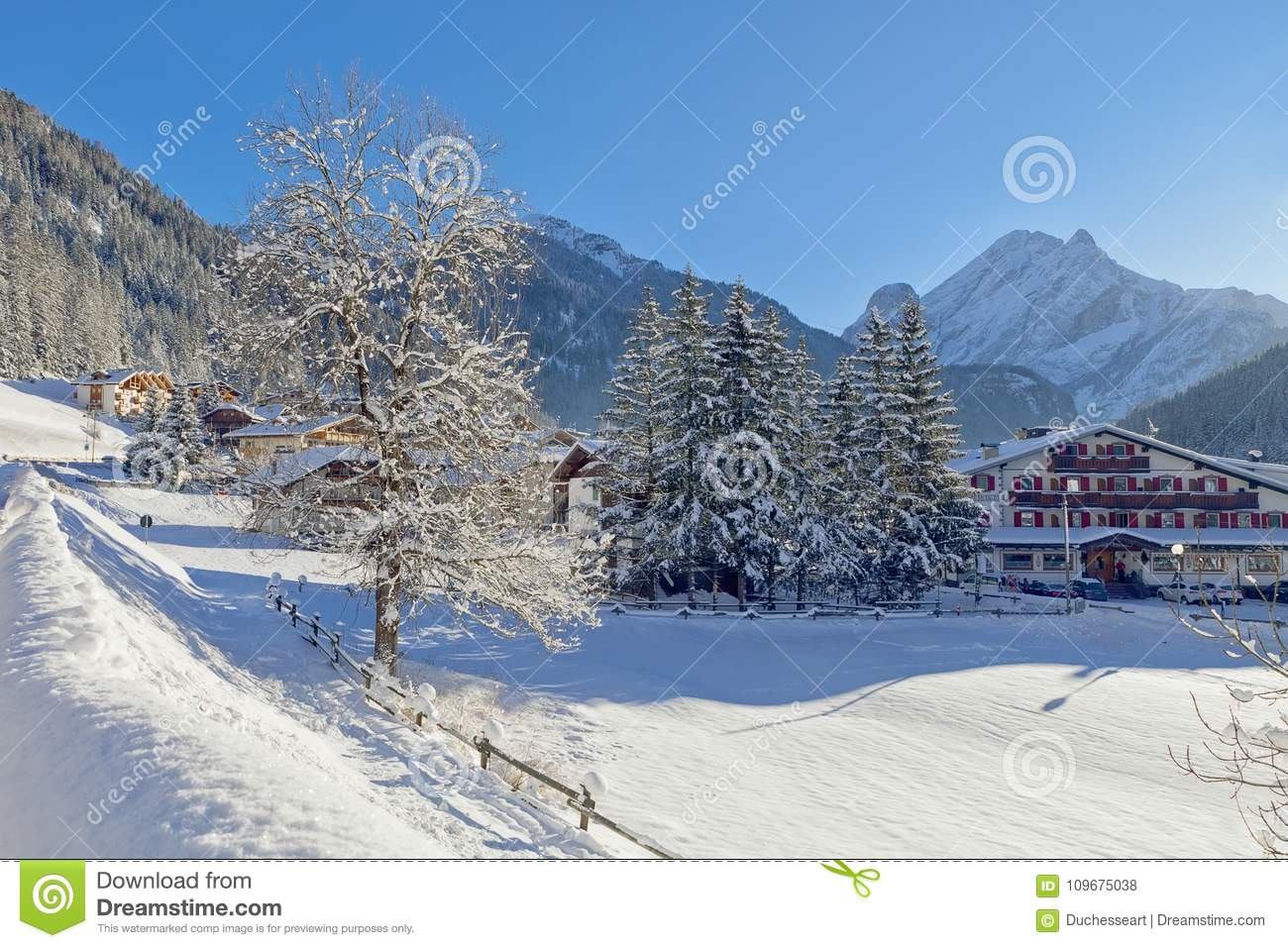 snowy alpine village in italy illuminated by sun with mountains in