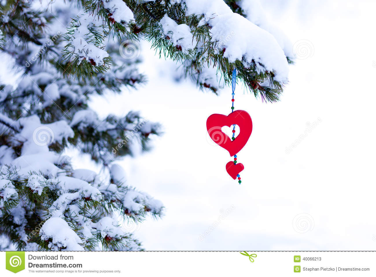 Snowy christmas tree red heart ornament stock image