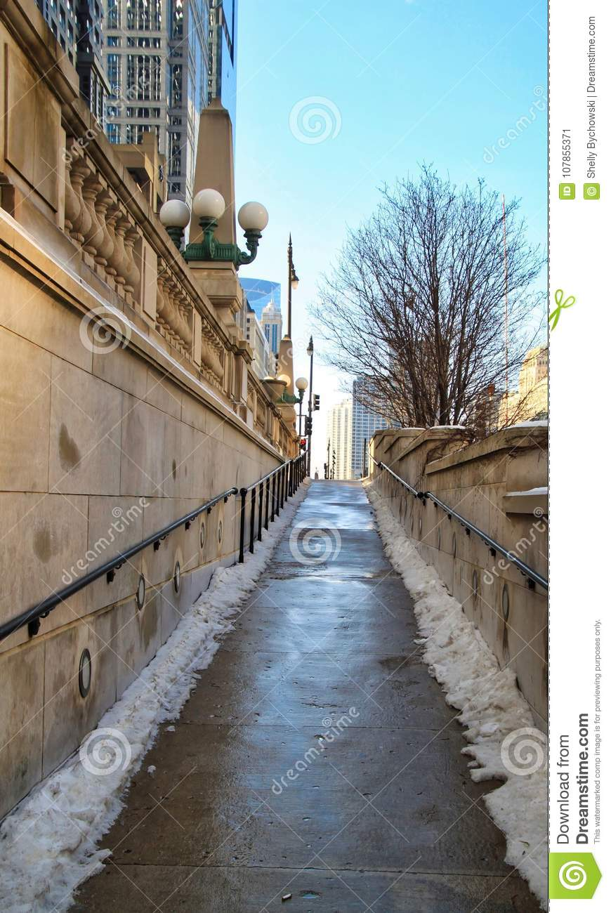 Snowy footpath leading up and away from the riverwalk in downtown Chicago Loop