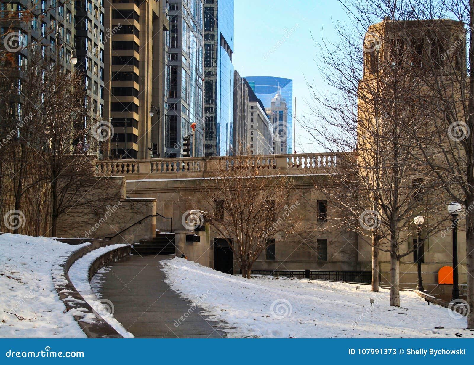 Snowy footpath bending away from the riverwalk in downtown Chicago Loop