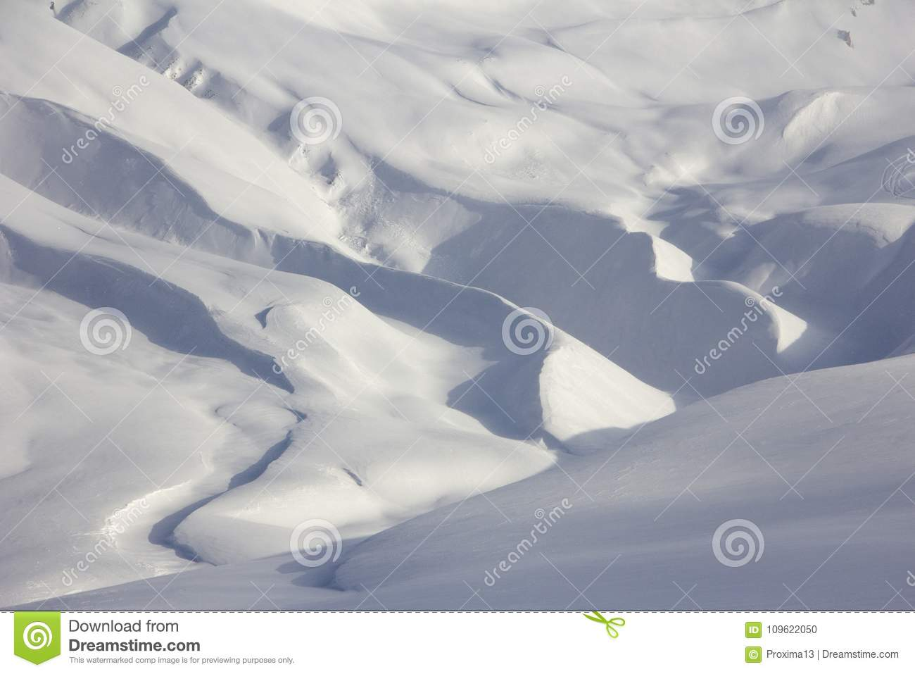 Snowy meandering mountain topography, shades of white and blue