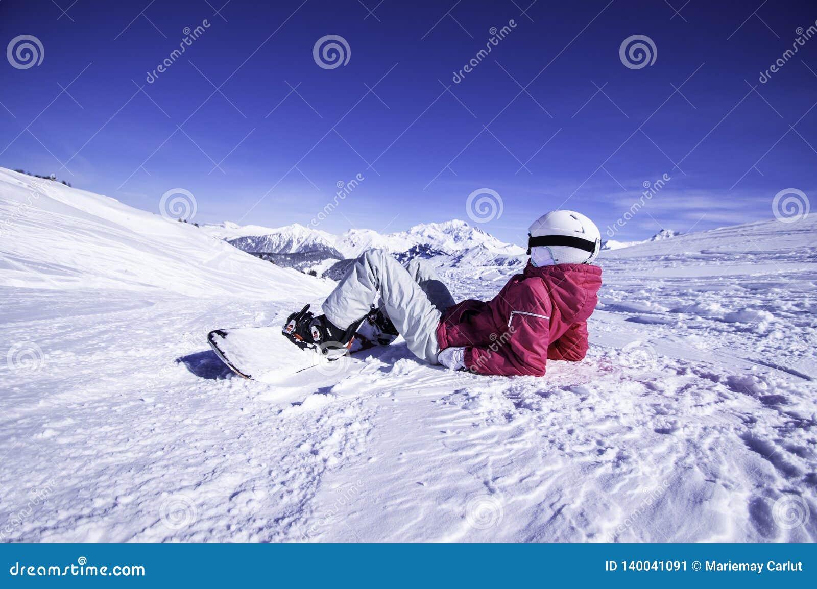 Snowy Mountain View Snowboarder der jungen Frau, der auf die Oberseite des Berges sich entspannt und die Ansicht aufpasst