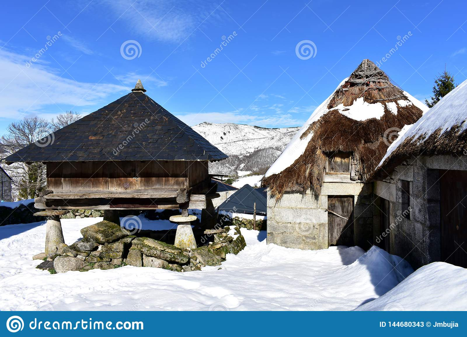 Snowy mountain village with ancient palloza houses made with stone and straw and galician granary horreo. Piornedo, Lugo, Spain.