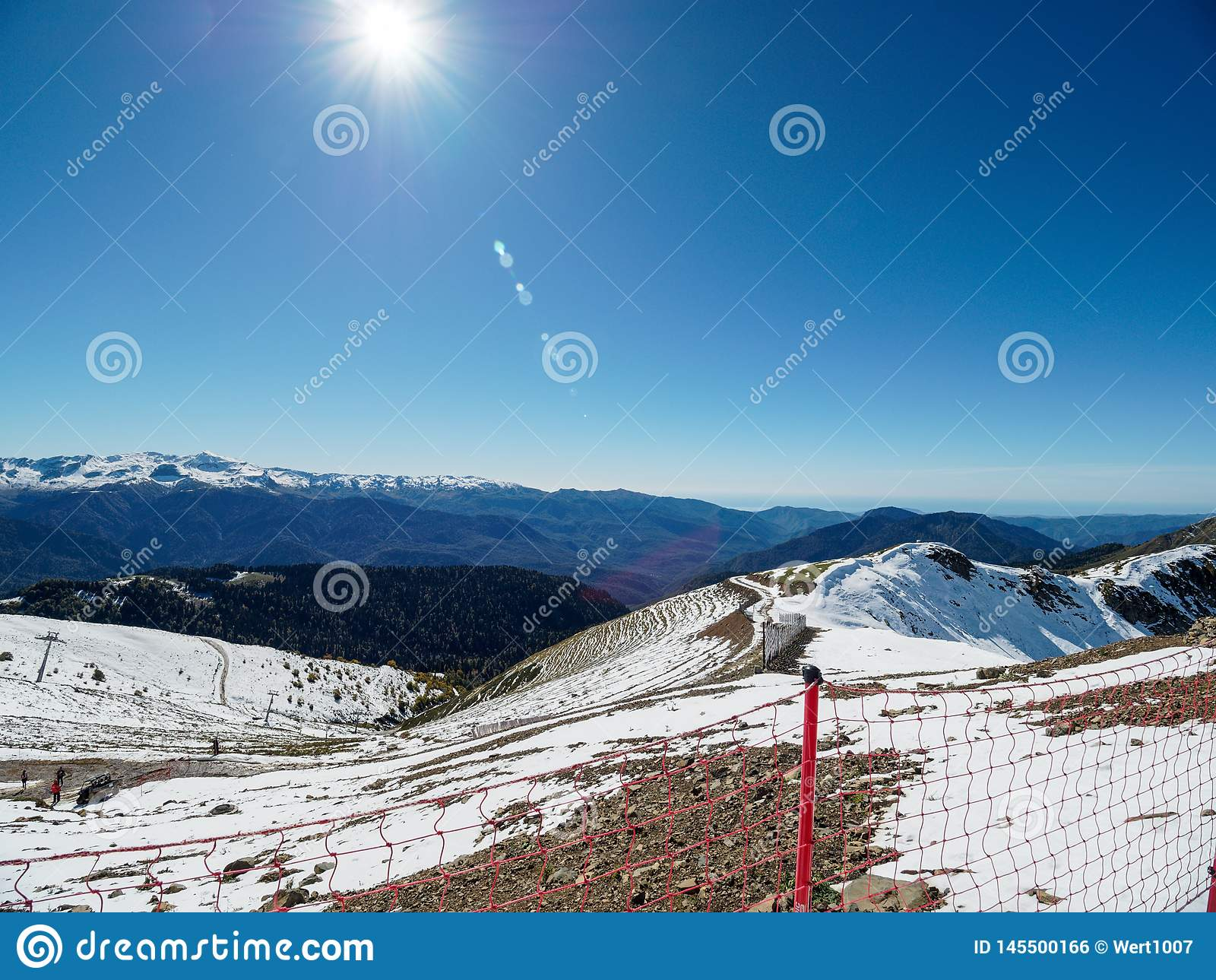 Snowy slope high mountains with ski lift. Blue sunny skies