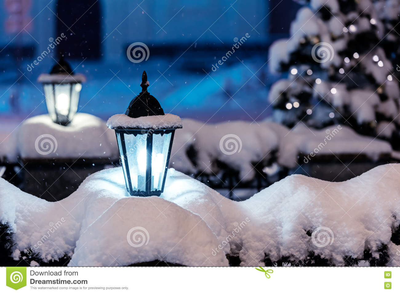 snowy street lamps in night city with fir-tree and christmas lights in background