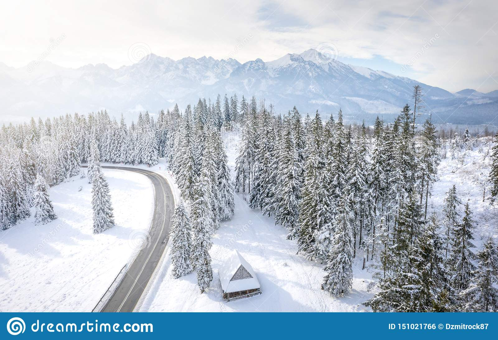 Snowy winter mountains landscape with frosty forest and road. Road to rocky mountain range. Wooden house in pine trees in mountain