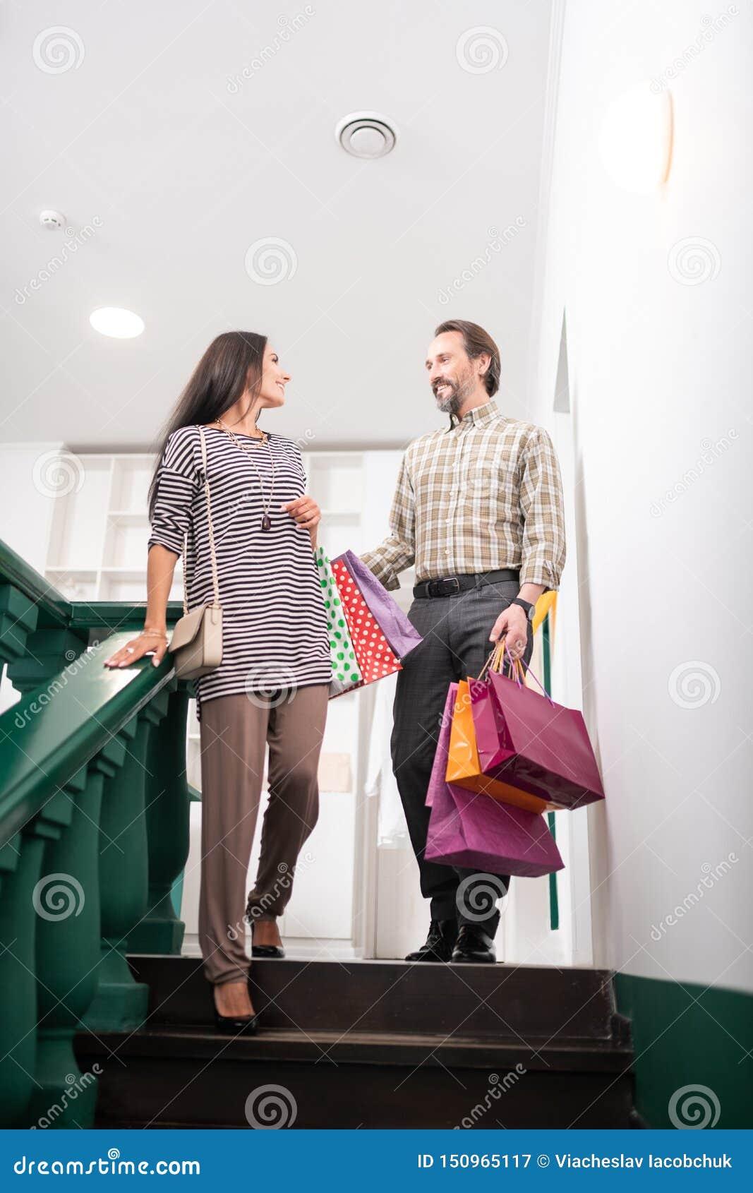 Snygg man som hjälper denhaired förtrollande charmiga kvinnan med shoppingpackar