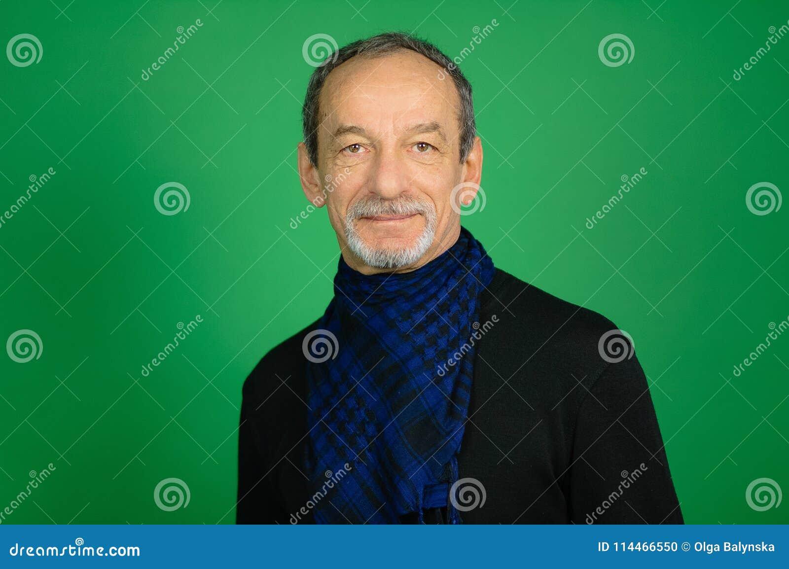 Snygg stilig hög gråhårig man med detklippte skägget i svart tröja och blå rutig halsduk omkring