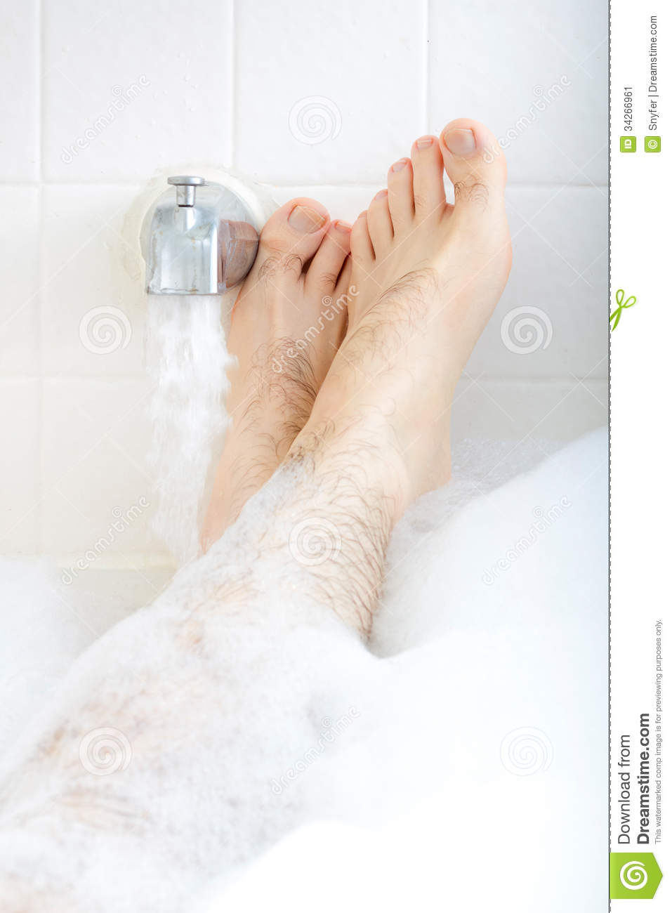 Male feet soaking in the bathtub with faucet runnng water.