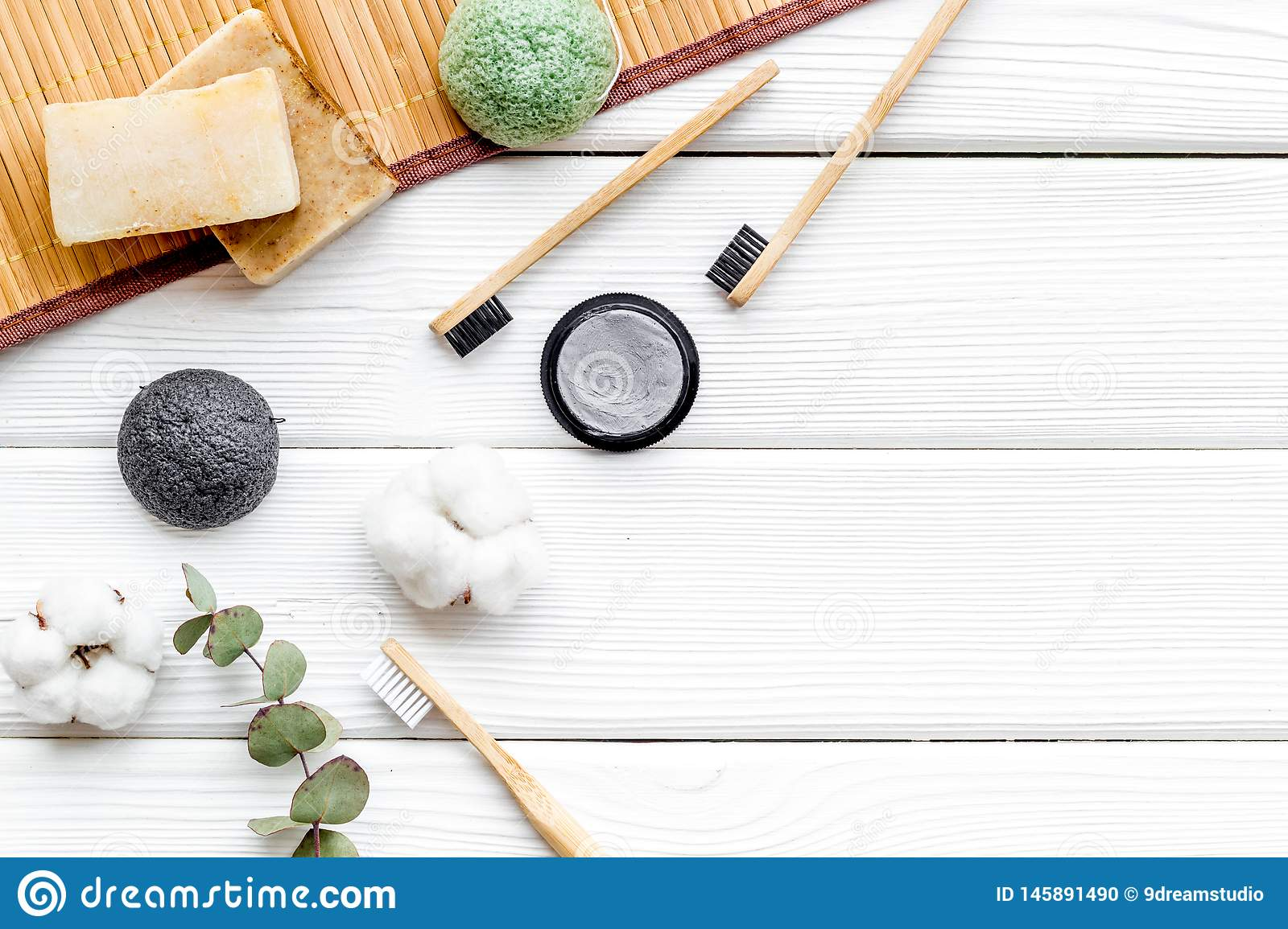 Soap, bamboo dental cleaning brush and toothpaste for zero waste lifestyle on white wooden background top view mock up. Soap, bamboo dental cleaning brush and stock photo