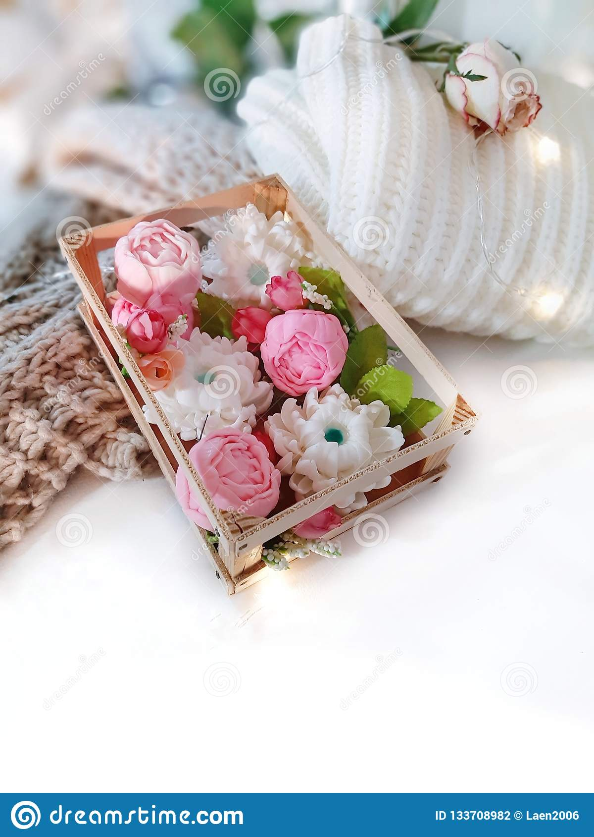 Soap floweres in box, knitted clothing, rose and lights on white background.