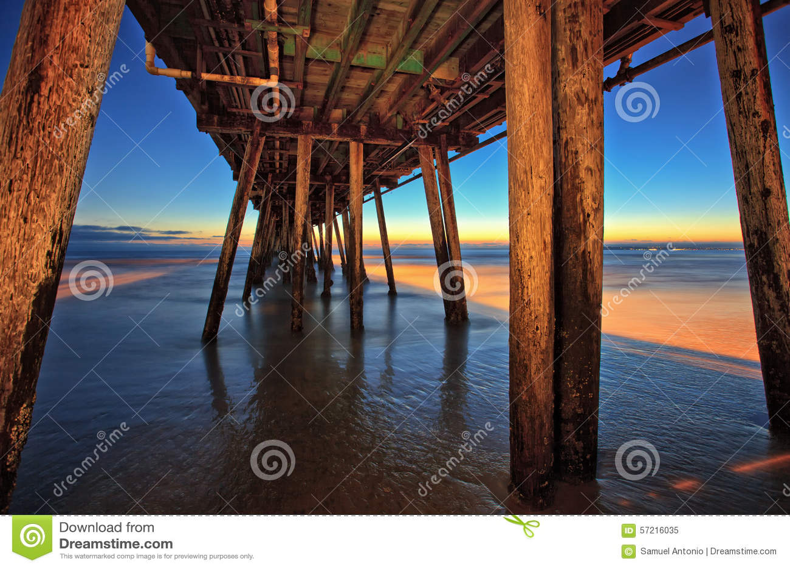 Sob o cais de madeira da praia no por do sol, praia imperial, Califórnia