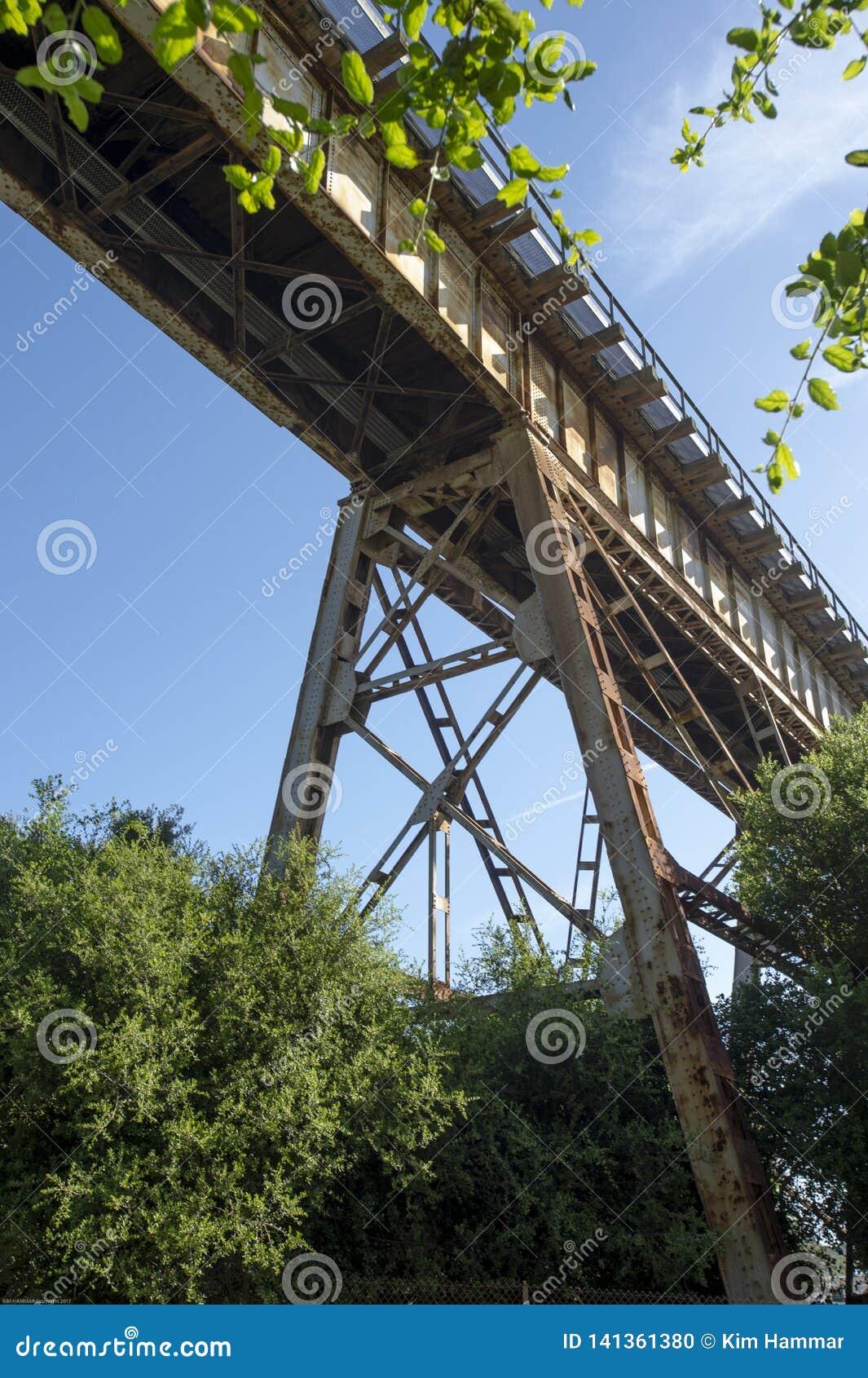 Sob uma treliça do trem contra o céu azul