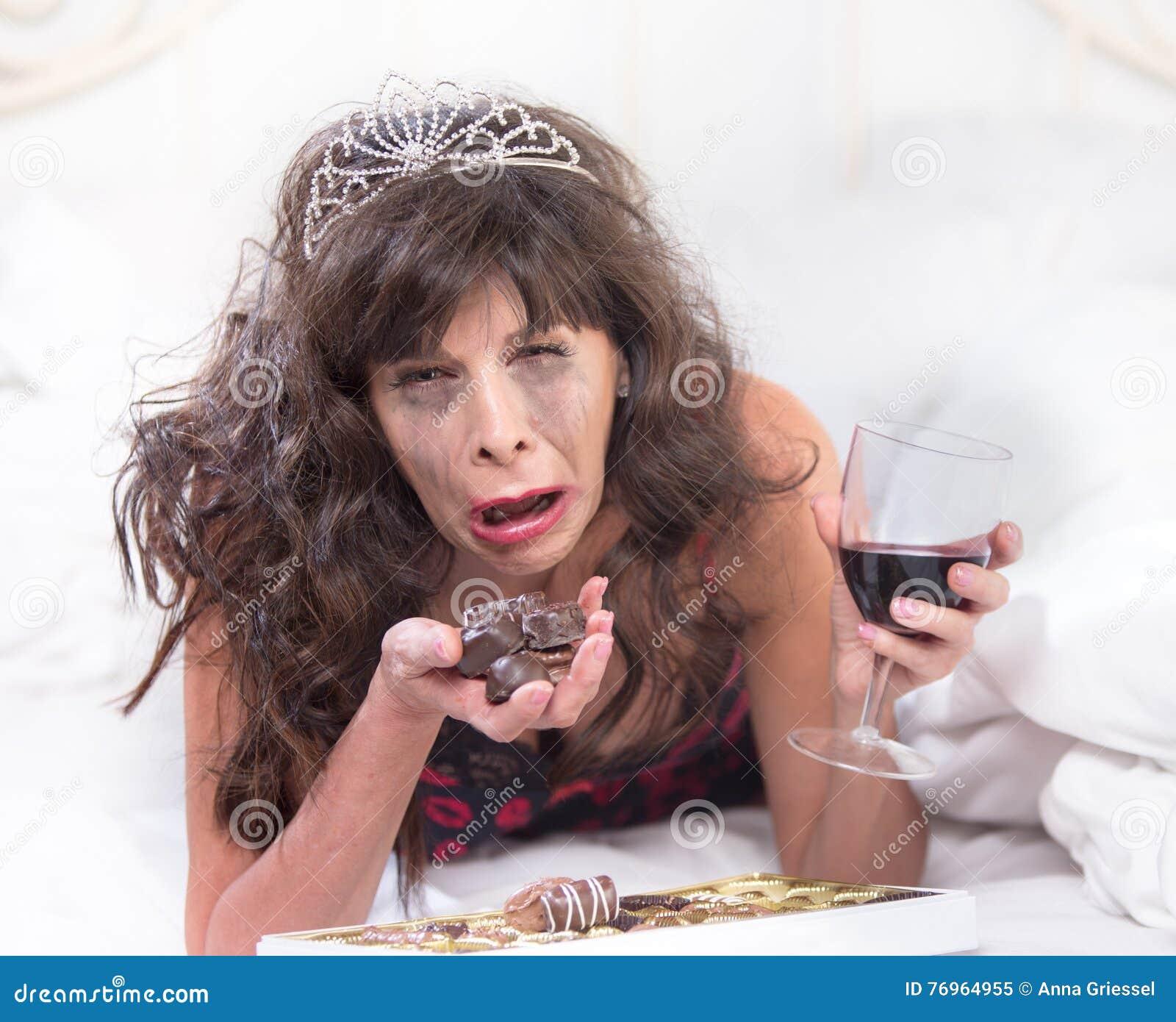 sobbing woman in tiara drinking wine and cramming chocolates in