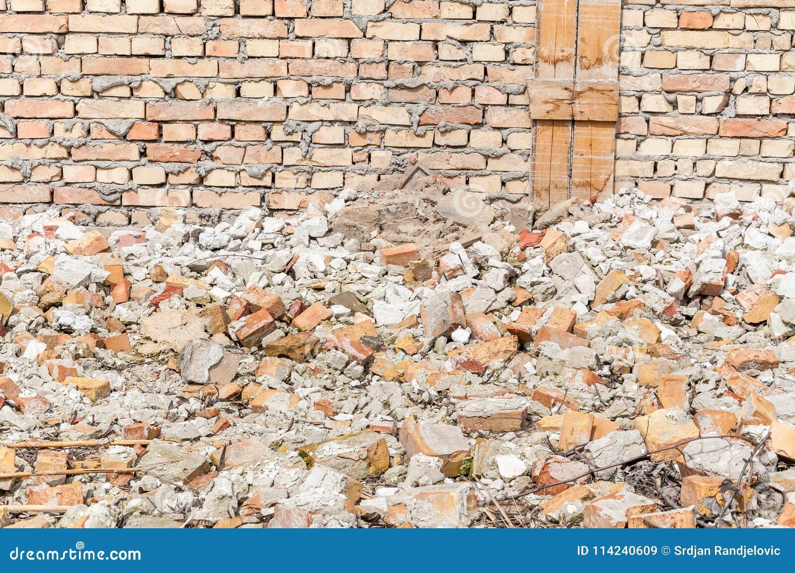 Sobras de dano do total do desastre do furacão ou do terremoto na casa ou na construção velha arruinada com a pilha dos tijolos
