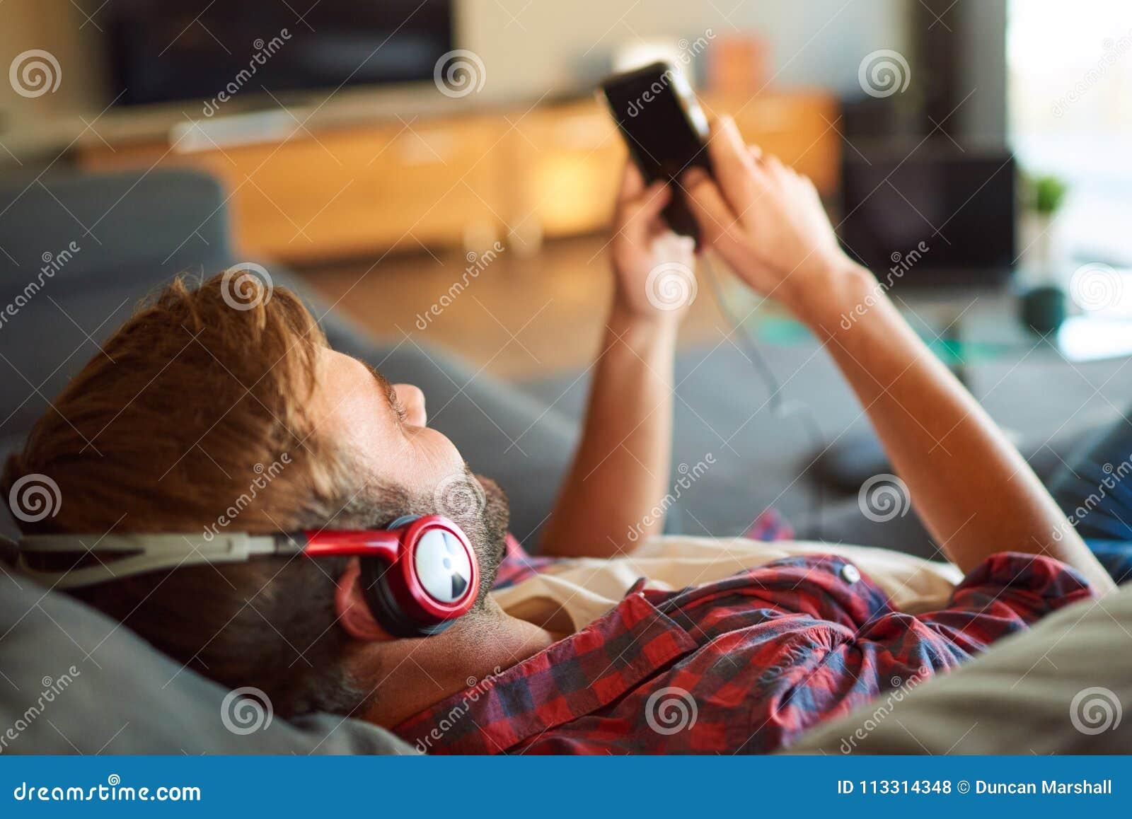 Sobre el hombro del individuo que escucha la música del teléfono