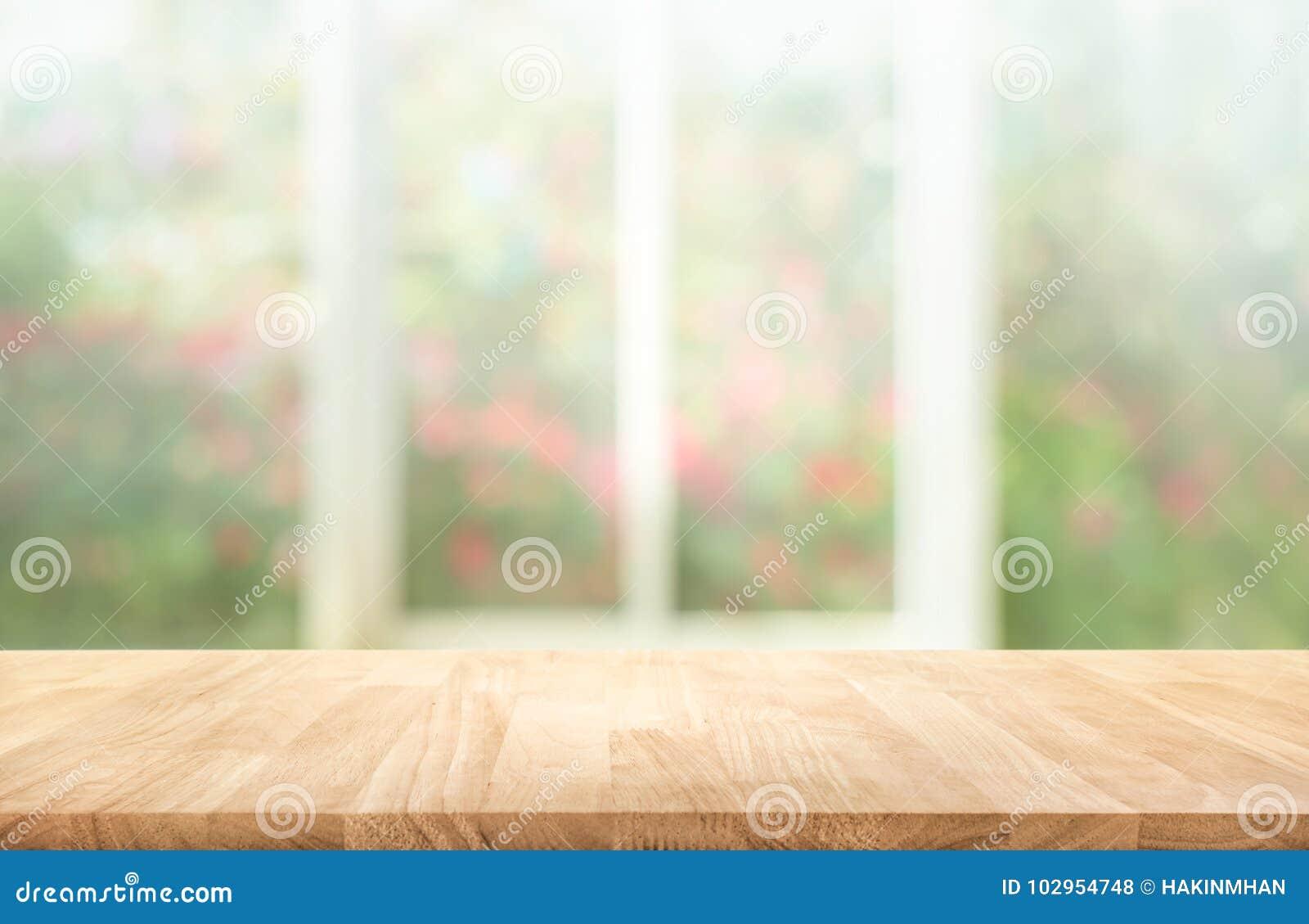 Sobremesa de madera en la falta de definición de la ventana con el fondo de la flor del jardín