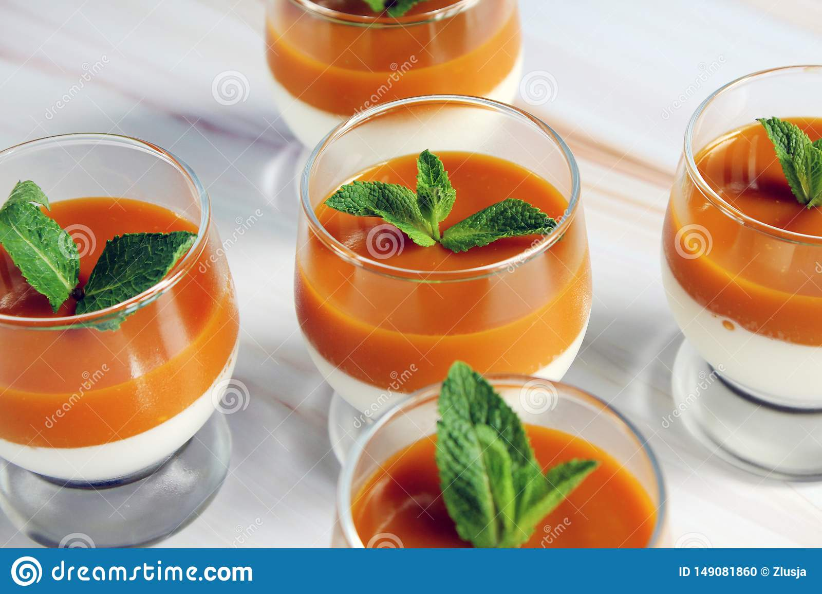 Sobremesa do cotta de Panna com pur? da manga com folhas de hortel? em um vidro em uma tabela de m?rmore